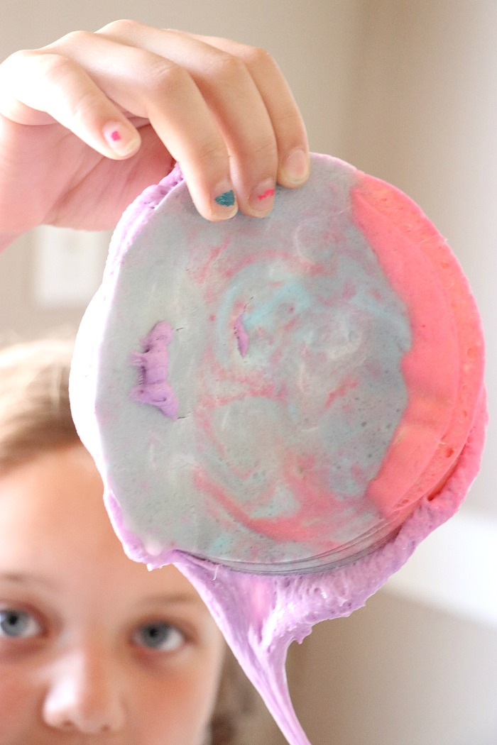 girl holding up pink and purple swirl iceberg slime